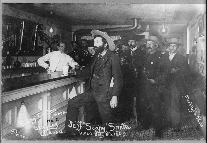 800px-Jefferson_'Soapy'_Smith_standing_at_bar_in_saloon_in_Skagway,_Alaska._July_29,_1989._LCCN2017656819